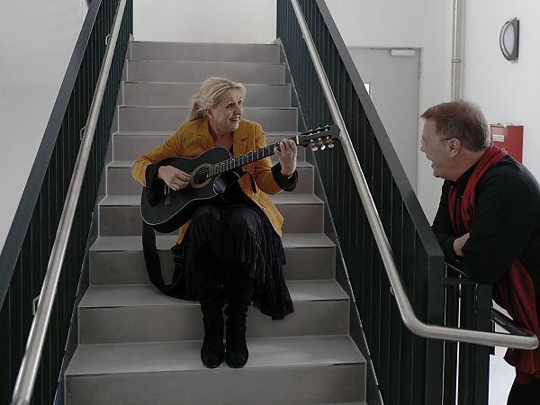 Rhetor Oliver Groß mit Claudia Pohel lächelnd auf Treppe mit Gitarre