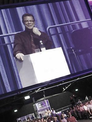 Oliver Groß am Rednerpult in voll belegter Halle