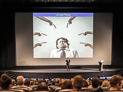 Oliver Groß auf der Bühne in voll belegter Halle